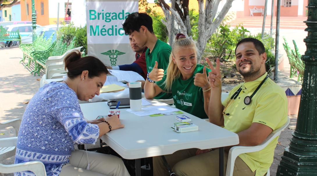 A group of high school students and a local doctor work together at a community healthcare outreach in Mexico.